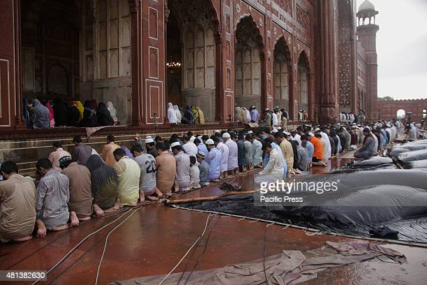 Pakistani faithful Muslim devotees take part in Eid prayers at the start of the Eid alFitr holiday marking the end of Ramadan at the historical...