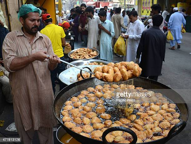 Pakistani faithful Muslims devotees break their fast and vendors preparing food items for Iftari on the 1st Ramadan during the Muslim fasting month...