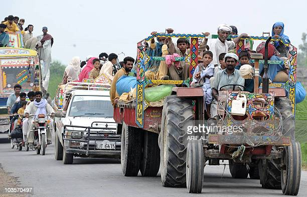 Pakistani families evacuate in a convoy of tractors pickup trucks buses and twowheelers a flash floodhit area in Mehmood Kot on August 5 2010...