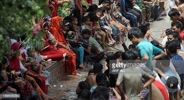 Pakistani families sit around a river canal on a hot day in Lahore on May 26 2013 Temperatures dropped by three to four degrees Celsius in many...