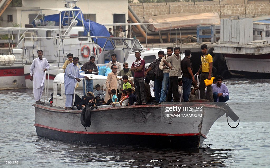 Pakistani families who abandoned their homes on the tiny island of Baba, an approximate 15-minute boat ride from Karachi, arrive on a private boat in Karachi on June 5, 2010. Hundreds of families are being shifted by the authorities from various islands and coastal neighborhoods of the southern port city to save them from tropical Cyclone Phet, which has killed 15 people and left two missing in Oman before barrelling towards Pakistan, a civil defence force official said. AFP PHOTO/Rizwan TABASSUM