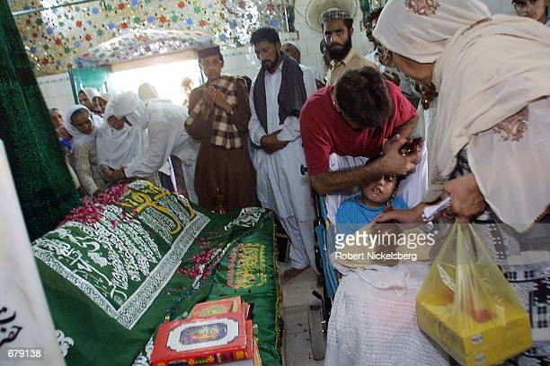 Pakistani family from London moves special wooden blocks around their paralyzed and mentally handicapped nineyear old boy's head October 25 2001 at...