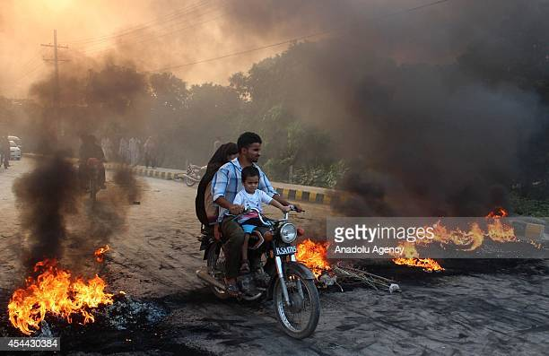 Pakistani family ride on bike as Supporters of the Pakistan TehreekeInsaf political party block the road with burning tires in Lahore Pakistan on...