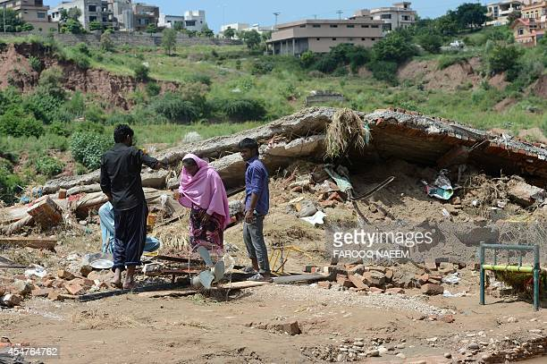 A Pakistani family stands next to their destroyed house following flooding in Rawalpindi on September 6 2014 More than 200 people in Pakistan and...
