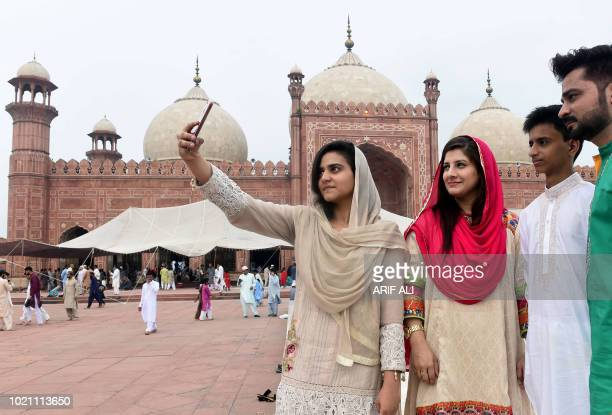 A Pakistani family takes a selfie after Eid alAdha prayers at the Badshahi Mosque in Lahore on August 22 2018 Muslims across the world are...