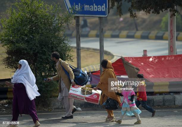 A Pakistani family walks along a road blocked by activists of the TehreekiLabaik Yah Rasool Allah Pakistan religious group during a week long protest...