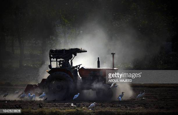 Pakistani farmer uses a tractor to prepare a field on the outskirts of Peshawar on September 28 2018