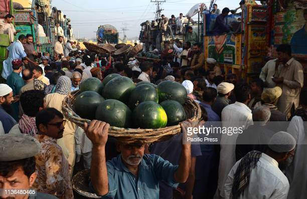 Pakistani farmers are busy unloading their trucks of watermelons at Badami Bagh Fruit Market. Local traders are coming from their outskirts areas to...