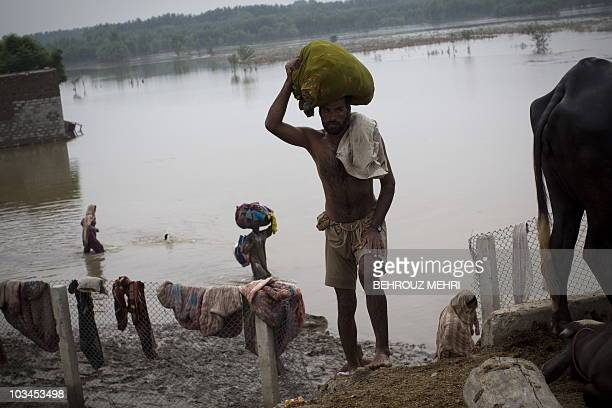 Pakistani farmers carry belongings from their destroyed houses to tents set on the motorway in the outskirts of Peshawar on August 6 2010 Pakistan's...