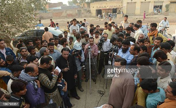 Pakistani farmers gather around media representatives following the execution of Ajmal Kasab who was the sole surviving gunman of the 2008 Mumbai...