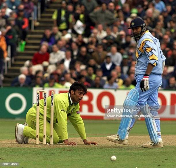 Pakistani fast bowler Shoaib Akhtar falls to the floor after a wicketless spell as Indian batsman Robin Singh looks on during the Super Six Cricket...
