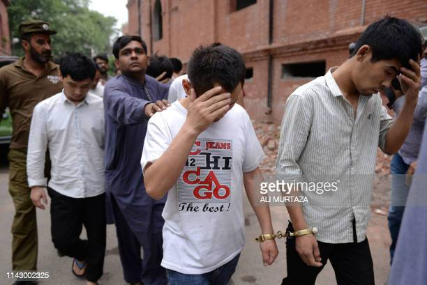 A Pakistani Federal Investigation Agency official and a policeman escort to a court handcuffed Chinese nationals accused of allegedly luring young...