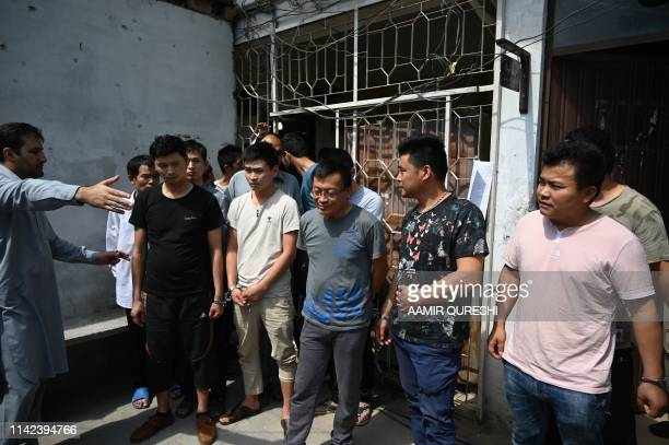 A Pakistani Federal Investigtion Agency official guides detained handcuffed Chinese nationals as they arrive to appear before a court for alleged...