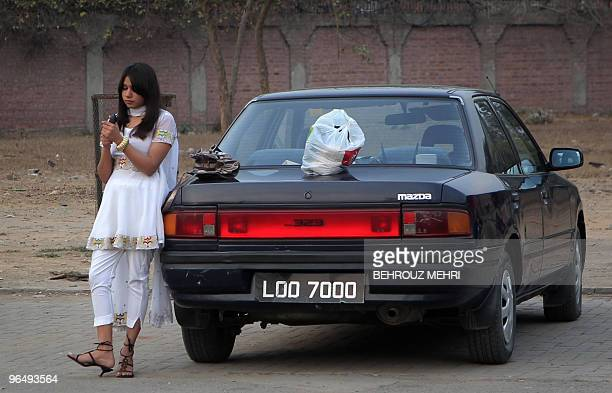 A Pakistani female student checks her mobile phone while waiting in the courtyard of a women's college for a pop concert to begin in Lahore on...