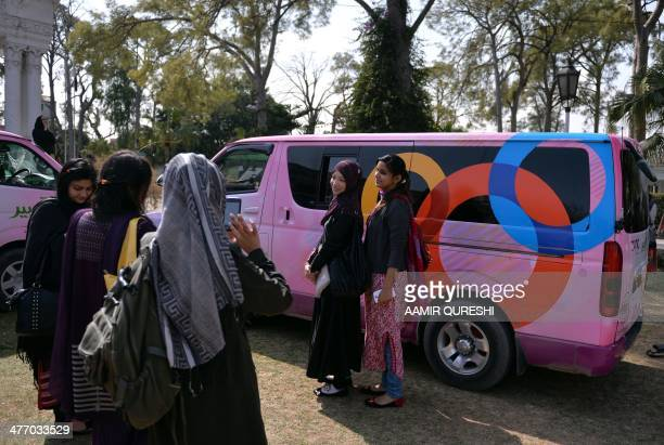Pakistani female university students gather around vans from the newly launched Tabeer Women Transport Service after attending a ceremony about the...