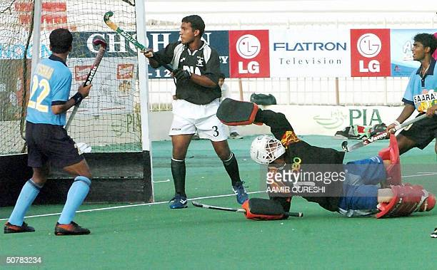 Pakistani field hockey team goalkeeper Mohammad Iqbal fails to stop a goal hit by Indian Thshar Handker as Pakistani Akhlaq Ahmed looks on during the...