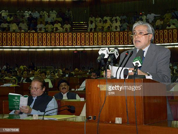 Pakistani Finance Minister Ishaq Dar presents the annual budget at the National Assembly as Prime Minister Nawaz Sharif reads a copy of the budget in...