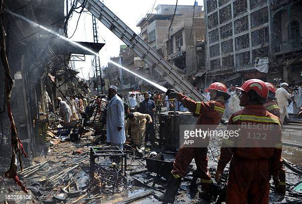 Pakistani firefighters extinguish a fire after a bomb explosion in the busy Kissa Khwani market in Peshawar on September 29 2013 A bomb explosion...