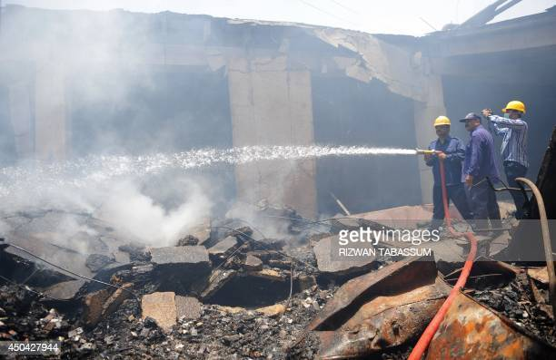 Pakistani firefighters lay water over the smouldering coldstorage facility at the Jinnah International Airport in Karachi on June 11 2014 Uzbek...