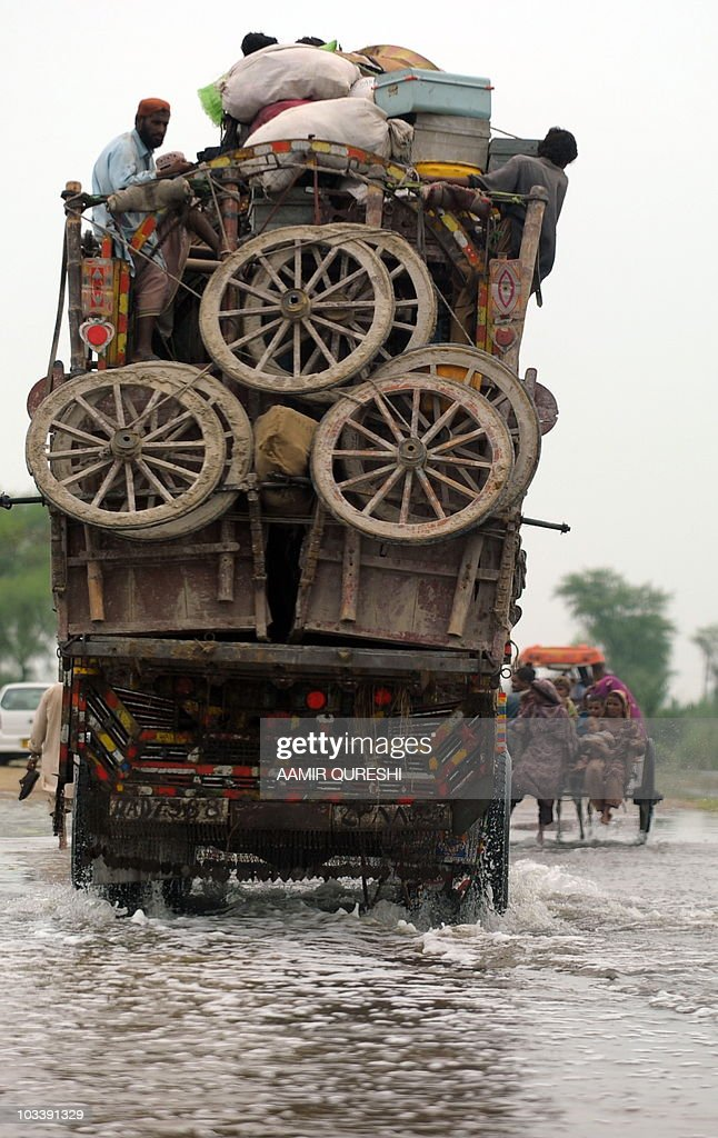 Pakistani flood servivors sit on top of a truck as they