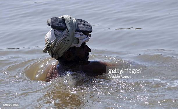Pakistani flood victim wade through a flooded area to move to a higher ground as his house is submerged in the floodwaters in Multan district of...