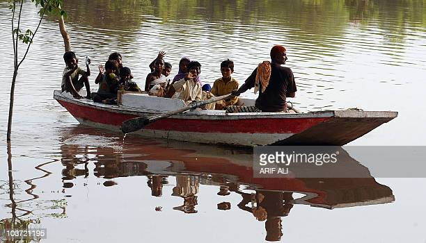 A Pakistani floodaffected family ride in a boat through floodwaters in Karam Dad Qureshi village in Dera Ghazi Khan district on August 27 2010...