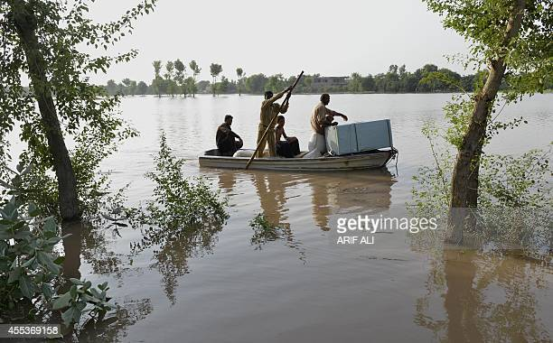A Pakistani floodaffected family rides a boat to reach dry ground in the outskirts of Multan on September 13 2014 The floods began in Kashmir after...