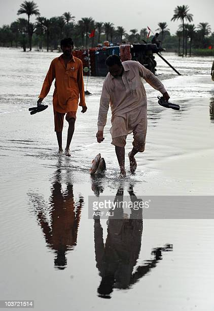 A Pakistani floodaffected villager carries fish caught from the floodwaters in Karam Dad Qureshi village in Dera Ghazi Khan district on August 27...