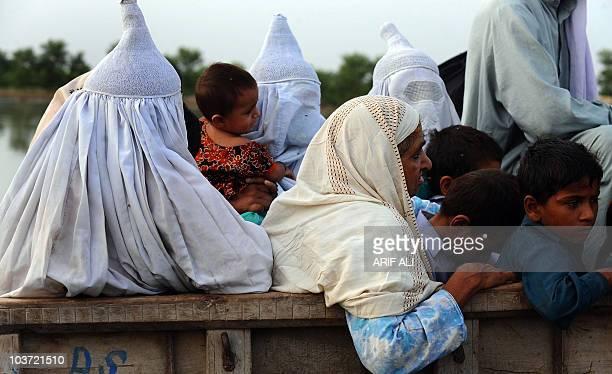 Pakistani floodaffected villagers travel on a truck through the Karam Dad Qureshi village in Dera Ghazi Khan district on August 27 2010 Pakistan...