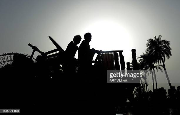 Pakistani floodaffected villagers travel with their belongings on a truck in Karam Dad Qureshi village in Dera Ghazi Khan district on August 27 2010...