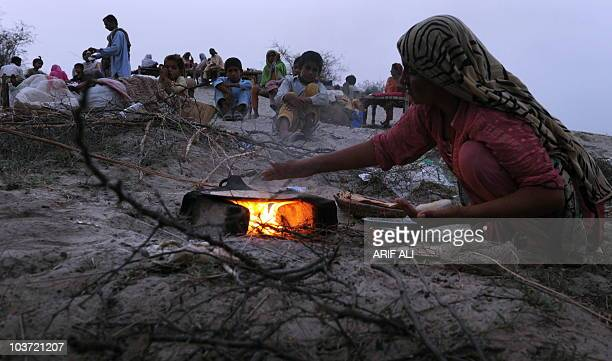 A Pakistani floodaffected woman prepares bread on a higher ground in the Karam Dad Qureshi village in Dera Ghazi Khan district on August 27 2010...