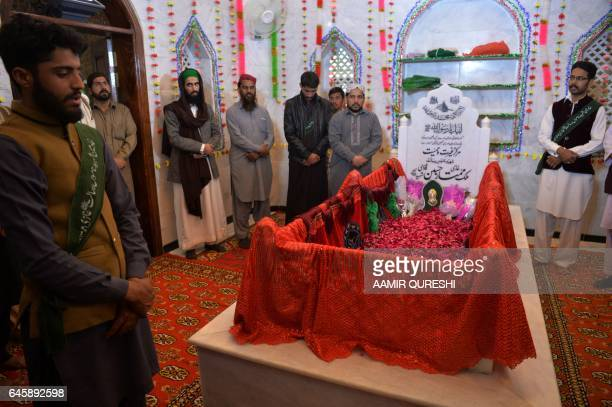 Pakistani followers stand as they pay their respects to Mumtaz Qadri who was hanged last year for the murder of a governor who criticized Pakistan's...