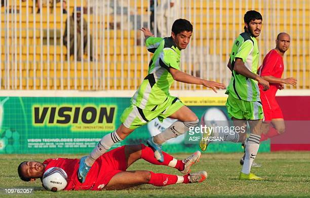 Pakistani football team player Mehmood Khan vies for th eball with Palestine's player Ismil Alamour during an International friendly in Karachi on...