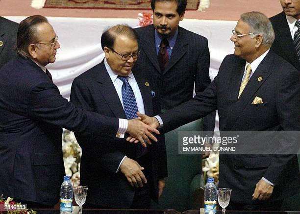 Pakistani Foreign Minister Khurshid Mahmud Kasuri and his Indian counterpart Yashwant Sinha shake hands as Bangladeshi Foreign Minister Morshed Khan...