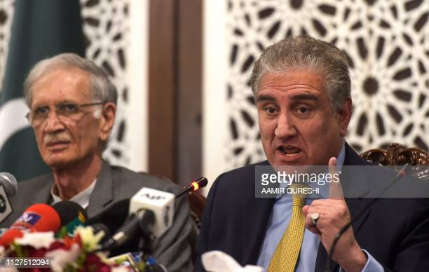 Pakistani Foreign Minister Shah Mehmood Qureshi speaks next to Defence Minister Pervez Khattak during a press conference at the Foreign Affairs...