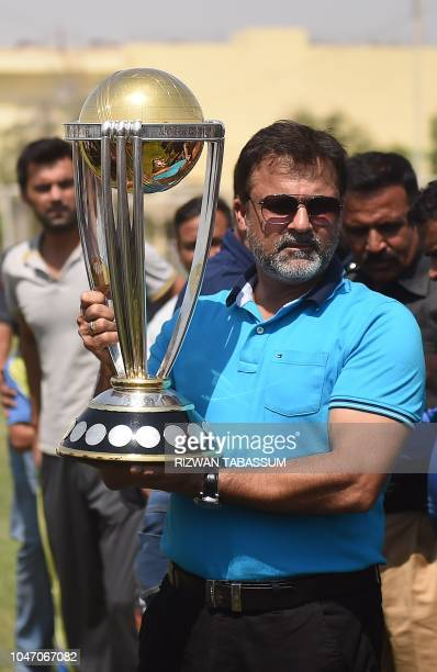Pakistani former cricketer Moin Khan holds the 2019 ICC Cricket World Cup trophy during a country tour event in Karachi on October 7 2018 The 2019...