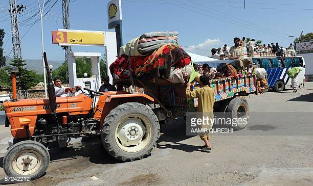 A Pakistani gasoline station employee fills a tank of a tractor carrying local residents as they flee from military operations against Taliban...