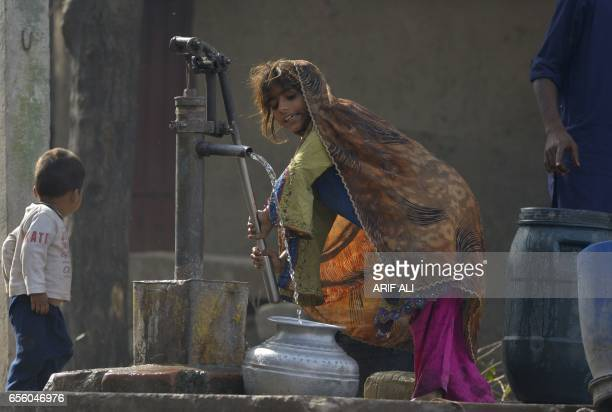 A Pakistani girl fills a pot with water from a hand pump on the outskirts of Lahore on March 21 ahead of World Water Day International World Water...