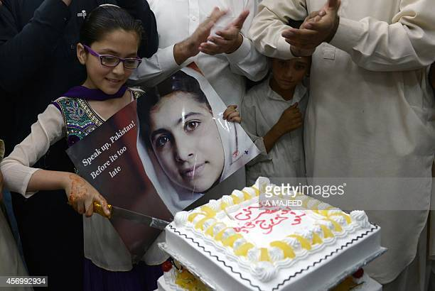 A Pakistani girl holds a photograph of child education activist Malala Yousafzai as she cuts a cake in celebration of Malala winning the Nobel Peace...