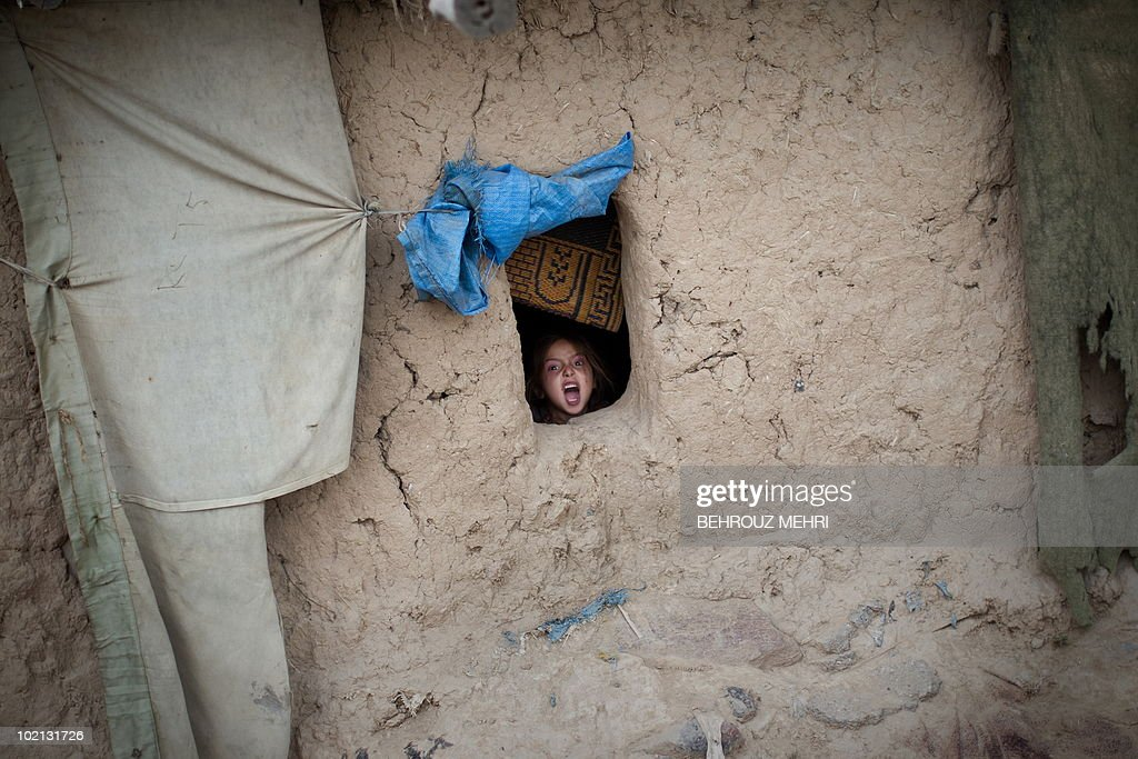 A Pakistani girl reacts to the photographer from the window of a mud house in a slum area in Islamabad on June 15, 2010. Pakistan approached the International Monetary Fund in 2008 and has secured a 11.3 billion USD standby loan in an effort to contain inflation and cope with a rapid depletion of reserves that were barely enough to cover nine weeks of import bills.