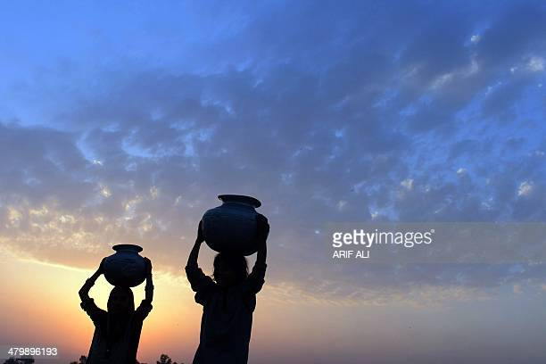 Pakistani girls carry water pots over their heads as they head for home during sunset on the outskirts of Lahore on March 21 on the eve of World...