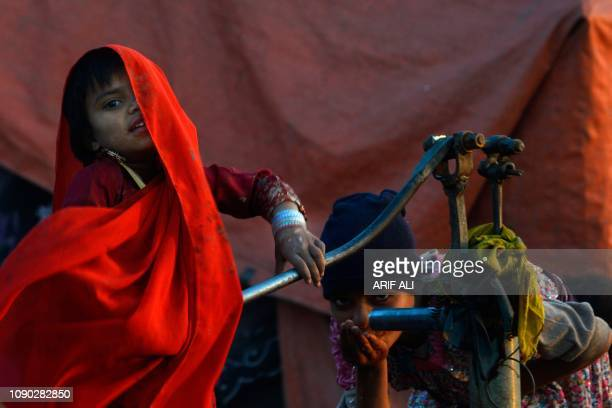 TOPSHOT Pakistani gypsy children drink water from hand pump in Lahore on January 27 2019