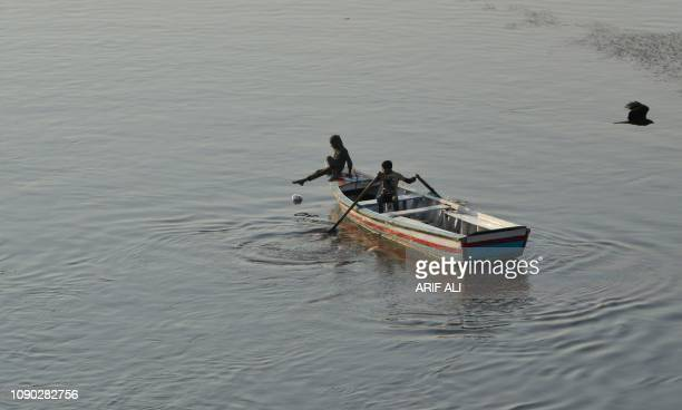 Pakistani gypsy children play on a boat in the Ravi river in Lahore on January 27 2019