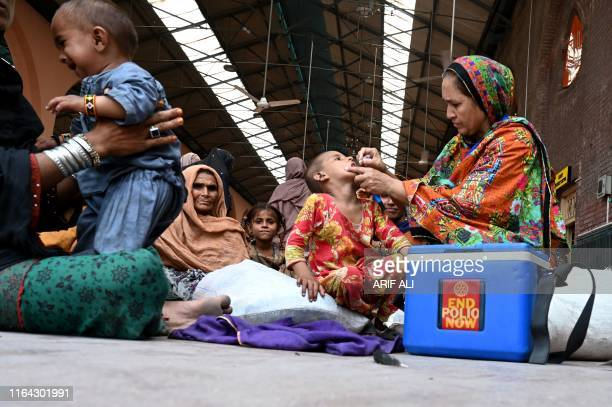 A Pakistani health worker administers polio drops to a child at a railway station during a polio vaccination campaign in Lahore on August 27 2019