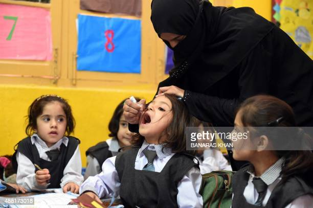 A Pakistani health worker administers polio drops to a child at a school during a polio vaccination campaign in Quetta on September 14 2015 Pakistan...