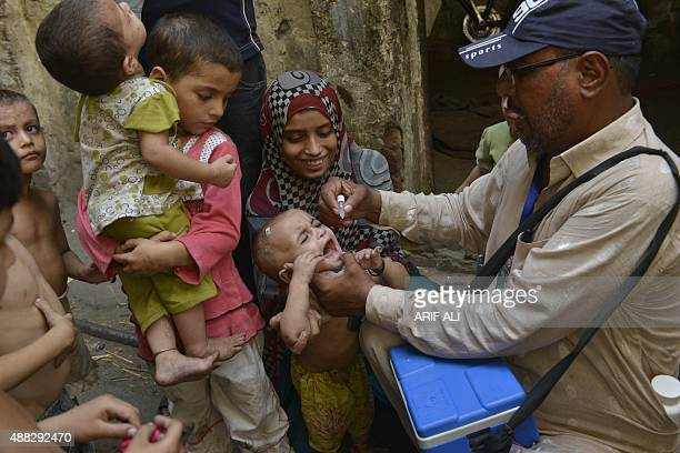 A Pakistani health worker administers polio drops to a child during a polio vaccination campaign in Lahore on September 15 2015 Pakistan is one of...
