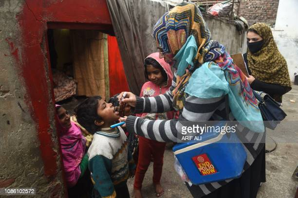 A Pakistani health worker administers polio vaccine drops to a child during a polio vaccination campaign at a slum area in Lahore on January 22 2019