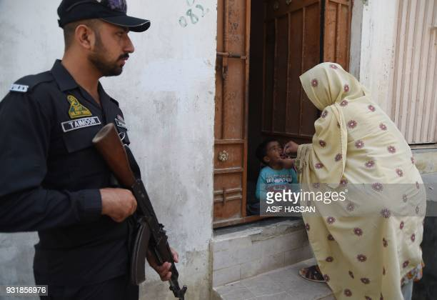 A Pakistani health worker administers polio vaccine drops to a child as a policeman stands guard during a polio campaign in Karachi on March 14 2018...