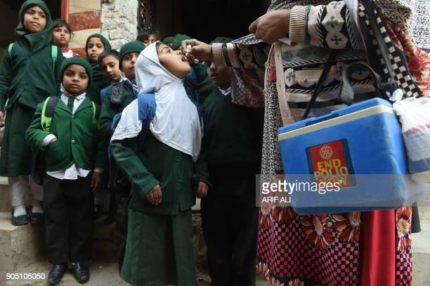 Pakistani health worker administers polio vaccine drops to school children during a polio campaign in Lahore on January 15 2018 Pakistan is one of...