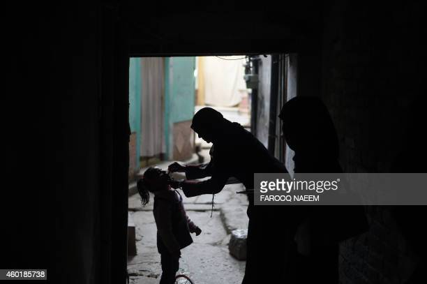 A Pakistani health worker administers the polio vaccine to a child during a vaccination campaign in Rawalpindi on December 9 2014 Gunmen on December...